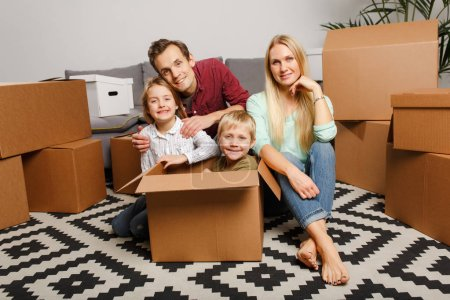 Photo for Image of young couple with children sitting on floor among cardboard boxes in new apartment - Royalty Free Image