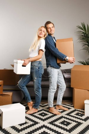 Photo for Photo of happy couple standing among cardboard boxes in new apartment - Royalty Free Image