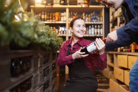 Photo pour Photo de femme vendeur avec bouteille de vin et acheteur en magasin - image libre de droit