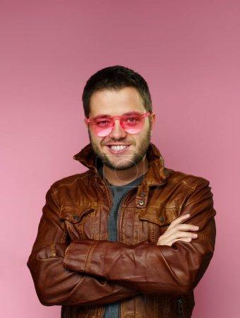 Photo pour Photo de brunette de sourire avec des lunettes roses, veste en cuir, avec des bras croisés sur le fond rose dans le studio - image libre de droit