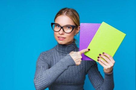 Photo pour Photo de femme dans des lunettes avec cahier dans les mains sur fond bleu vierge - image libre de droit