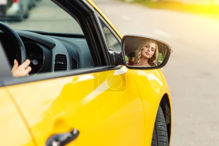 Photo for Photo of female driver reflecting back in yellow taxi mirror. Sunlight effect. - Royalty Free Image