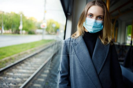 Photo for Young blonde in medical mask looking at camera standing at window in bus. Coronavirus epidemic - Royalty Free Image