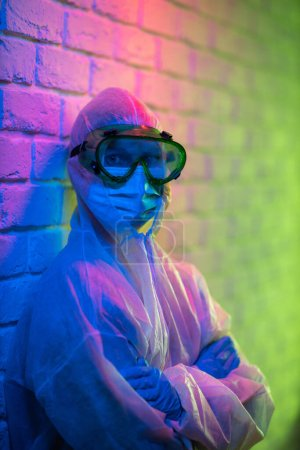 Photo for Young doctor in protective suit and glasses looking at camera near brick wall background. Neon color - Royalty Free Image