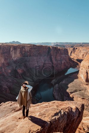 A travel girl hiking in Horseshoe bend in Arizona. A girl in a brown Fedora hat and a green poncho. Blonde girl sitting Horseshoe Bend in Glen Canyon National Recreation Area
