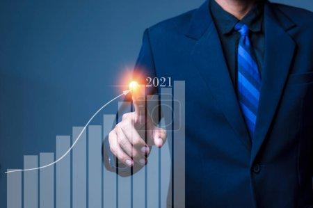 Photo pour Croissance en 2021 concept année. Main de l'homme d'affaires plan de croissance et d'augmentation des indicateurs positifs dans son entreprise. - image libre de droit