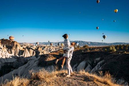 Foto de Una pareja enamorada en Cappadocia. La pareja viaja por el mundo. Vacaciones en Turquía. Luna de miel en Cappadocia. Feliz pareja que viaja. Viaje de luna de miel. Vuelos en globo de aire caliente. Mujer en brazos de un hombre - Imagen libre de derechos