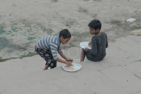 Photo for Little boys eating on street during religious festive day in India - Royalty Free Image