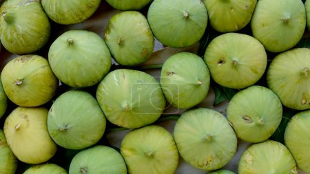Photo for Closeup of unripe green figs in wooden crate - Royalty Free Image
