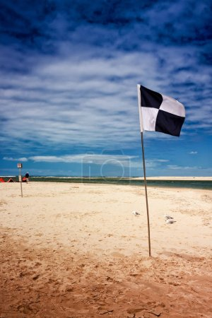 A black and white flag marks the surf zone at a beach in Caloundra, Queensland, Australia. The day is a bit windy, there are not many people on the beach.
