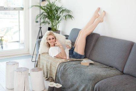 Photo pour Concept de détente, de confort, de loisirs et de personnes - jeune femme heureuse lisant un livre et allongée sur le canapé à la maison . - image libre de droit