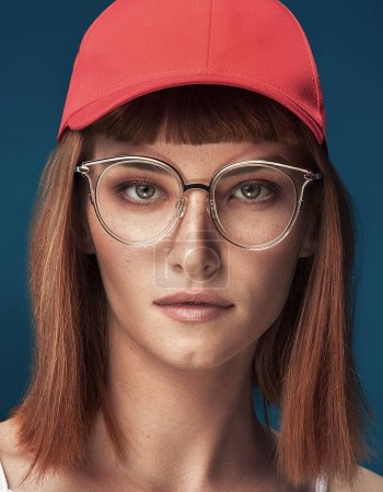 Photo for Portrait of attractive young redhead woman with fashionable eyeglasses and cap. Girl looking at camera. Blue background. - Royalty Free Image