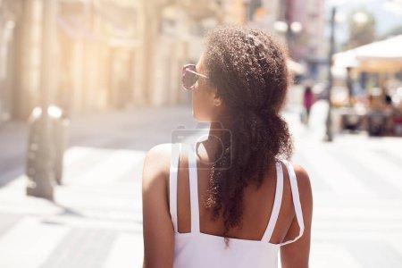 Foto de Vista trasera de la hermosa chica afroamericana con el pelo largo y rizado caminando por la calle italiana en el soleado día de verano. Tiempo libre de vacaciones . - Imagen libre de derechos