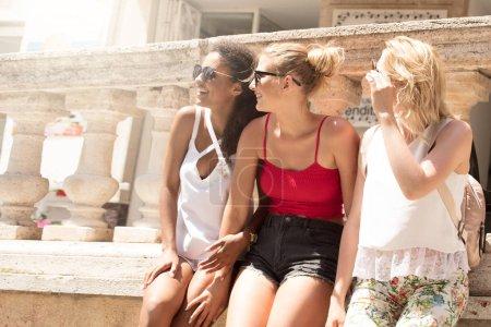 Photo pour Belles jeunes filles blondes heureuse et multiraciale femme afro-américaine s'amusant, en souriant. Vacances Italie. Groupe de jeunes filles de passer du temps ensemble à jour ensoleillé. - image libre de droit