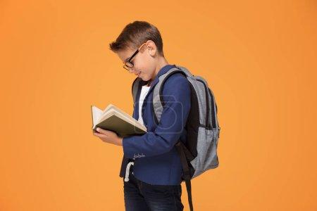Foto de Escuela niño de anteojos con pie de mochila sobre fondo naranja, con libro, sonriendo. - Imagen libre de derechos