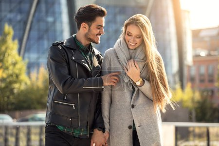 Young couple dating in the city. Blonde beautful woman and handsome man in fashionable clothes , autumn season.