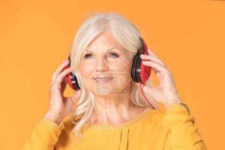 Photo pour Senior belle femme à l'écoute de sa musique préférée à travers de gros écouteurs rouges, profiter du son . - image libre de droit