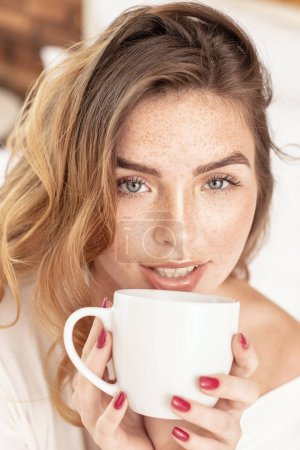 Photo for Beauty portrait od delicate caucasian lady with white coffee cup. Beautiful ginger woman with long hair and with freckles . - Royalty Free Image
