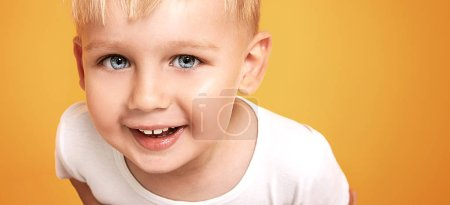 Photo for Portrait of a confident happy little kid smiling, looking at camera, isolated over orange background in studio. - Royalty Free Image
