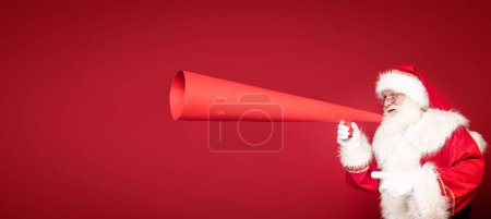 Photo for Photo of real Santa Claus screaming through a huge red megaphone.. Merry Christmas and Happy New Year concept. A lot of copy space. - Royalty Free Image
