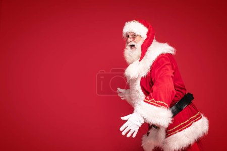 Photo for Happy Santa Claus smiling, looking at camera, posing on red studio background. Merry Christmas & New Year's Eve concept. - Image. A lot of copy space. - Royalty Free Image