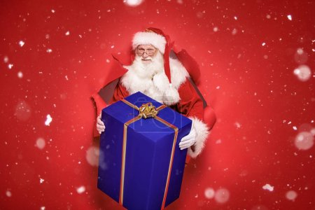 Photo for Santa Claus , the real one, comes out of the red studio background with a big gift. Christmas time. - Royalty Free Image