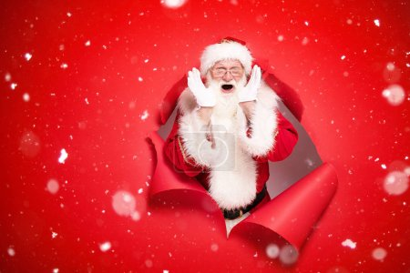 Photo for Santa Claus , the real one, comes out of the red studio background with emotional face. Christmas time. - Royalty Free Image