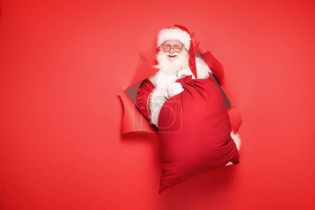 Photo for Santa Claus , the real one, comes out of the red studio background with a big gift. Christmas time.A lot of copy space. - Royalty Free Image