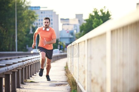 Young athlete man is jogging on the bridge.