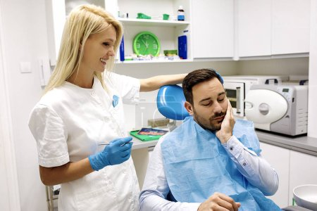 Female dentist and young man patinet in dentist office.