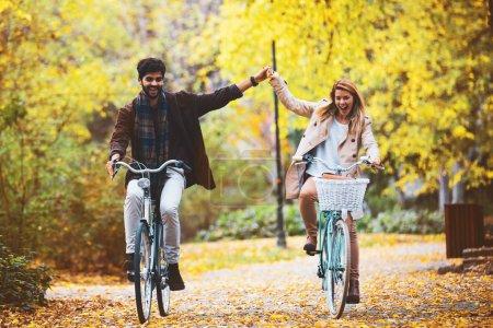 Photo pour Jeune couple souriant profitant de l'automne dans le parc . - image libre de droit
