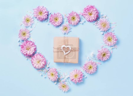 Photo for Heart symbol made of pink flower with gift box on a blue pastel background - Royalty Free Image