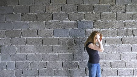 Photo for Desperate unhappy woman by the wall. the concept of stress and hopeless. - Royalty Free Image