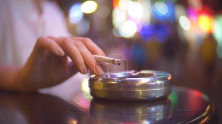 Photo pour Une femme célibataire s'assoit dans un café à l'extérieur des locaux, fumant une cigarette, sur fond de rue bondée brouillant le fond . - image libre de droit