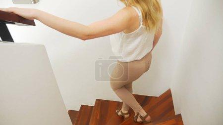 Photo pour Gros plan, jambes féminines en pantalon beige moulant et sandales à talons marchant le long d'un escalier moderne en bois . - image libre de droit