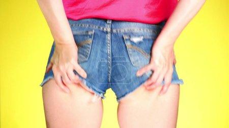 Photo pour Fille en short court jeans bleu. Vue rapprochée de l'arrière. Style frais l'été. - image libre de droit