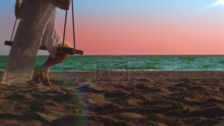Photo for A happy blonde girl in a white dress and lace cape is swinging on a rope swing, on the beach by the sea - Royalty Free Image