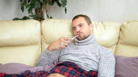 Photo pour Jeune homme malade dans un pull sous un plaid avec une fièvre vérifie sa température avec un thermomètre à la maison . - image libre de droit
