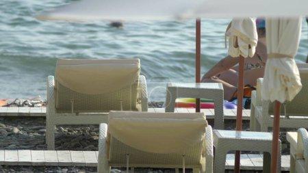Photo pour Fond flou. chaises longues et parasols sur la plage, personnes méconnaissables au repos . - image libre de droit
