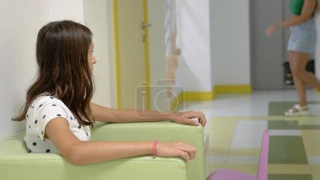 Photo pour La fille est assise dans le hall de la clinique pour enfants, attendant un rendez-vous avec le médecin. concept d'examen médical, suivi de la santé, examen préventif des médecins - image libre de droit