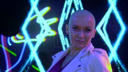 Photo pour Soirée club. La vie nocturne. chauve belle fille dansant dans un club dans les rayons colorés d'une discothèque néon lumières . - image libre de droit