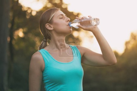 Photo for Beautiful woman enjoys drinking water during exercise.Image is intentionally toned. - Royalty Free Image
