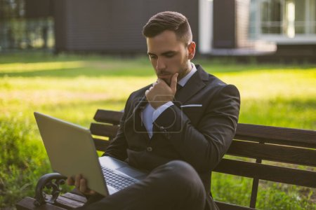 Photo for Worried businessman using laptop while sitting outdoor.Toned image. - Royalty Free Image