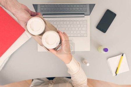 Photo pour Homme apportant du café dans des tasses en papier à collègue femme - image libre de droit