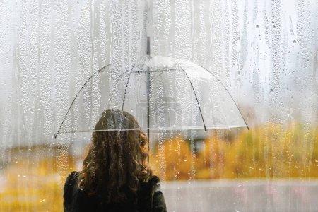 Foto de Una silueta de mujer con paraguas transparentes a través de una ventana húmeda con gotas de lluvia. Otoño - Imagen libre de derechos