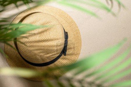 Photo pour Chapeau de paille d'été sur le sable à travers les branches de palmier et de palmier d'ombre. Voyage, vacances, concept d'été. Vue du dessus. - image libre de droit