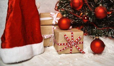 Geschenkschachteln und Weihnachtsmützen unter dem Weihnachtsbaum mit schönen, glänzenden Dekorationen