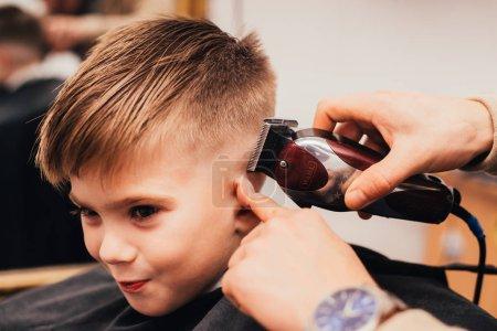 Photo pour Image recadrée de coiffeur faisant coupe de petit garçon au salon - image libre de droit