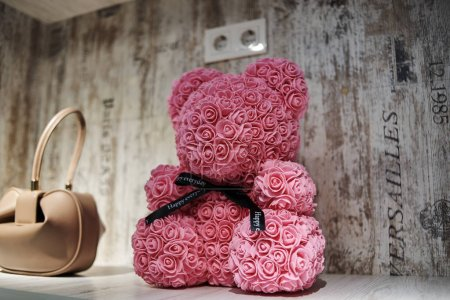 Photo for Decorative bear made of pink roses in clothing store - Royalty Free Image