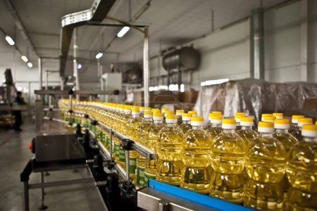 Photo for Sunflower oil in the bottle moving on production line. Shallow dof - Royalty Free Image